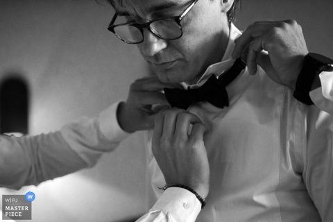 Foto en blanco y negro de dos hombres que ayudan al novio con su corbata de lazo de un fotógrafo de bodas de Bucarest, Rumania.