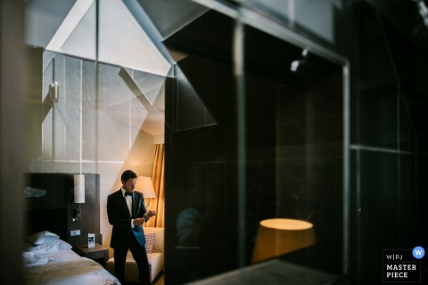 Photo of the groom getting ready with the window reflecting geometric shapes by a Lower Saxony, Germany wedding photographer.