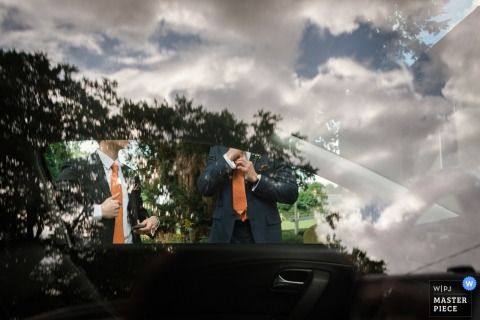 Photo détaillée de deux hommes se tenant de l'autre côté d'une voiture alors que le ciel et les nuages se reflètent à l'extérieur du véhicule par un photographe de reportage de mariage basé à Kent, en Angleterre.