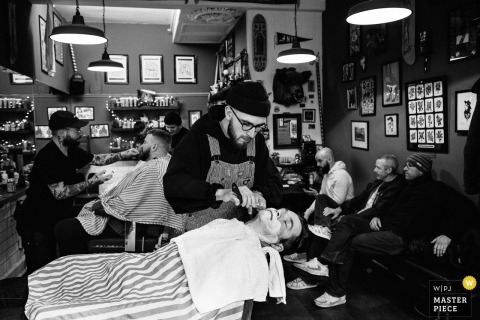 Black and white photo of the groom getting a shave at a barber shop by a Scotland wedding reportage photographer.