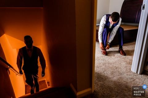 Photo du jour du mariage à Los Angeles, en Californie, du marié qui attache sa chaussure dans une pièce pendant qu'un homme monte l'escalier à côté de la pièce.