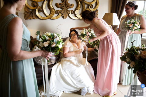 Photo of bridesmaids helping the bride get ready by a West Yorkshire, England wedding reportage photographer.