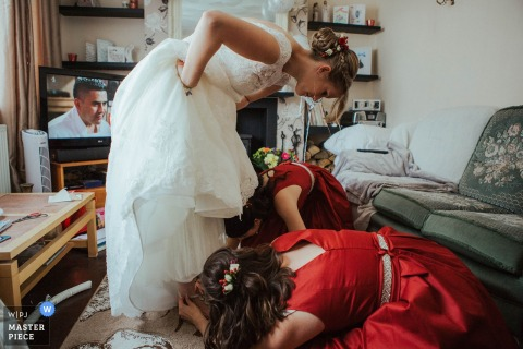 Photo of two bridesmaids helping the bride with her shoes by a Kent, England wedding reportage photographer.