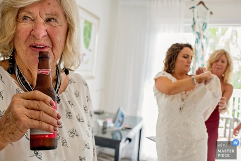 A woman helps the bride with her dress as another stands holding a beer in this photo by a Key West, FL wedding photographer.