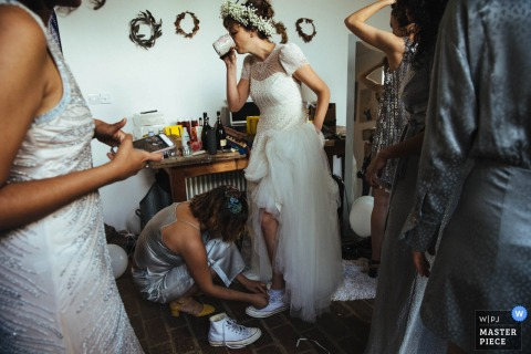 A woman helps the bride put on her shoes in this photo by a London, England wedding reportage photographer.
