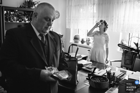 The bride takes a drink before the ceremony as a man flips through his wallet in this black and white photo by a Warsaw wedding photographer.