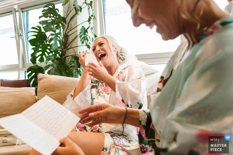 The bride and a bridesmaid get emotional as they read a card before the ceremony in this photo by a Devon, England wedding reportage photographer.