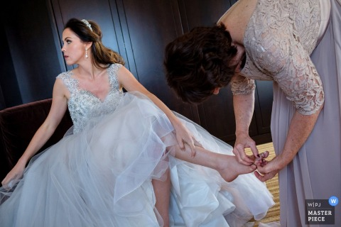 The bride sits with one leg crossed over the other as a woman helps her get ready in this photo by a San Diego, CA wedding photographer.
