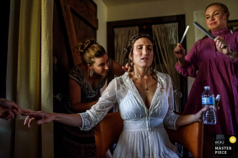 Women help the bride get ready as she sits in a chair in this photo by a San Diego, CA wedding photographer.