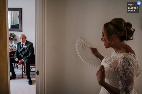 The bride walks down the hallway to see her father before the ceremony in this photo by a London, England wedding reportage photographer.