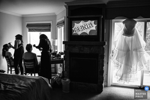 Two women get their makeup done as the bride's gown hangs in the window in this black and white photo by a New Jersey wedding photographer.