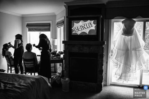 Zwei Frauen lassen sich schminken, während das Kleid der Braut in diesem Schwarzweißfoto eines Hochzeitsfotografen aus New Jersey im Fenster hängt.