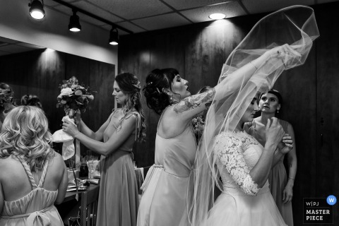 A woman flips the bride's veil over her head as the bride and bridesmaids get ready in this black and white photo by a Carson City, NV wedding photographer.