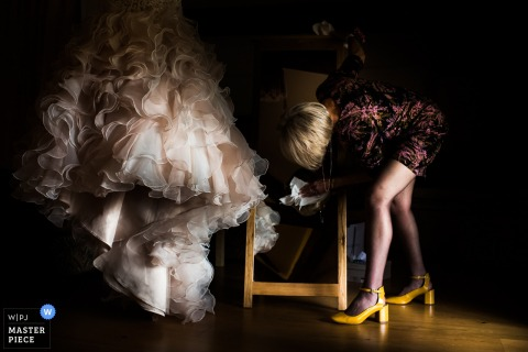 A woman cleans a mirror as the bride's gown hangs beside her in this photo by a Devon, England wedding reportage photographer.