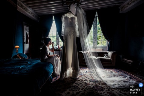 Photo of the bride sitting on the end of the bed with her wedding dress hanging in front of her by a Paris, France wedding photographer.