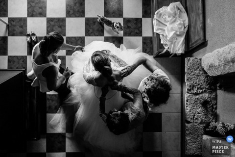 Black and white photo shot from above of three women helping the bride with her gown by a Leon wedding photographer.