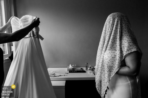 Black and white photo of the bride wearing a cloth over head as another holds up her dress preparing to help her into it by a Rotterdam wedding photographer