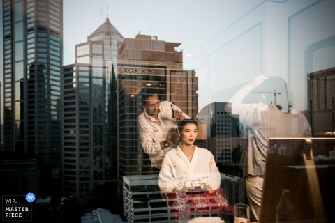 Photo taken through a window of the bride getting her hair done with skyscrapers reflected in the glass by a London, England wedding reportage photographer.
