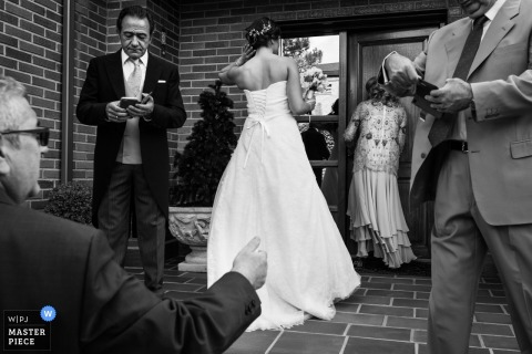 Madrid, Spain wedding day photograph of many guests doing various things such as using their cell phones and talking