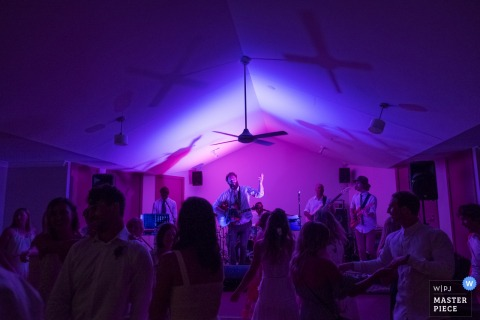 Musicians play on a stage as guests dance in blue and purple light in this photo by a New South Whales, Australia wedding photographer.