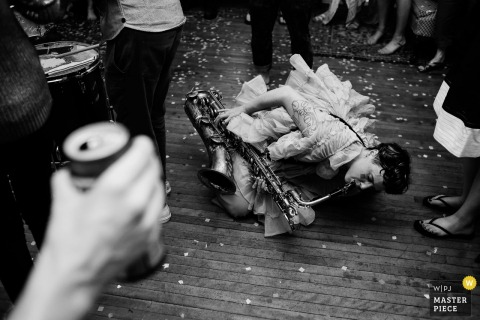 The bride plays a saxophone as she kneels down on the floor in this black and white photo by a Tunbridge, VT wedding photographer.