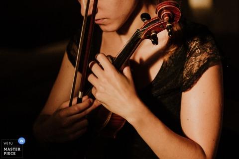 De foto van het detail van een vrouw die een viool houdt door een het huwelijksfotograaf van Lazio.