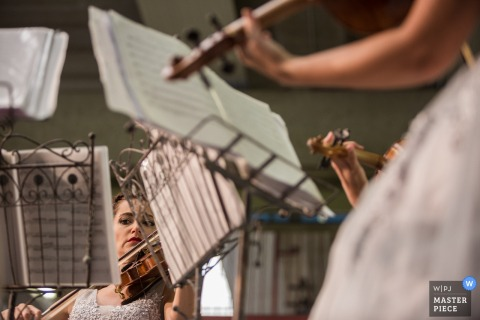 Women sit in front of music stands as they play violins in this photo by a Venice wedding photographer.