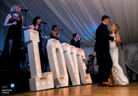 """Musiker singen, während die Braut und der Bräutigam vor einem Zeichen tanzen, das """"LIEBE"""" in diesem Foto durch einen Hochzeitsfotografen des Britisch-Columbia, Kanada liest."""