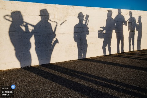 Photo of shadows of the band members playing music against a white stone wall by a Porto, Portugal wedding photographer.