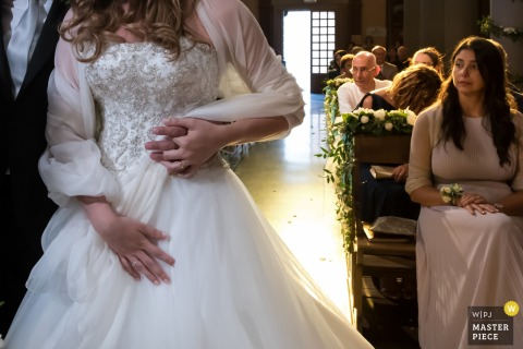 The bride holds the groom's hand around her waist during the ceremony in this photo by a Lombardy wedding photographer.