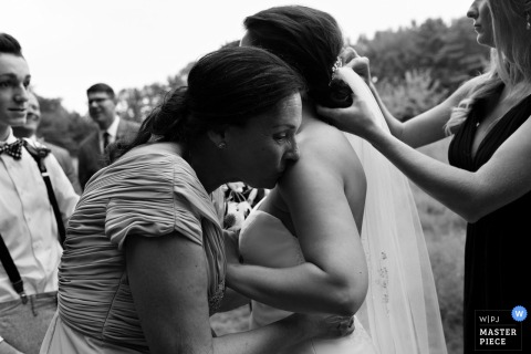 A woman kisses the bride's shoulder as another helps her with her hair in this black and white photo by a Maine wedding photographer.