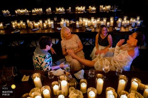 Panna młoda siedzi z gośćmi, gdy jeden z nich masuje stopę w holu recepcyjnym, otoczony świecami na tym zdjęciu przez fotografa ślubnego z Charleston.