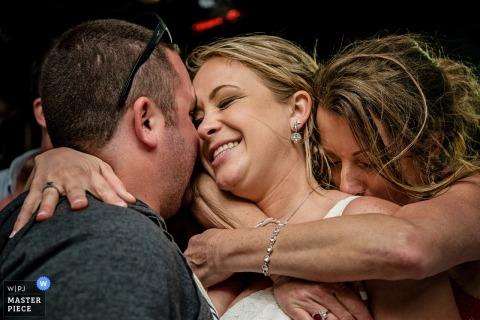 Een man en een vrouw omhelzen de bruid tussen hen in deze foto door een het huwelijksfotograaf van Key West, FL.