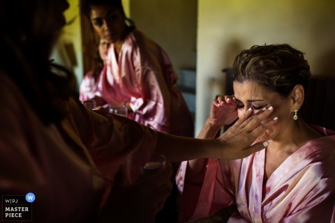 A bridesmaid wipes the bride's tear away as they all get ready in this photo by a Florence wedding photographer.