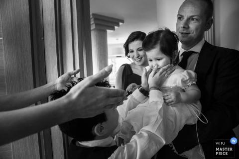 Een man houdt een klein meisje omhoog als een jonge jongen haar gezicht raakt en een vrouw reikt naar haar in deze zwart-witfoto door een trouwfotograaf uit Calabrië.