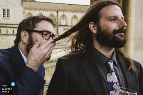 A man smells another man's long hair in this photo by a North Yorkshire, England wedding reportage photographer.