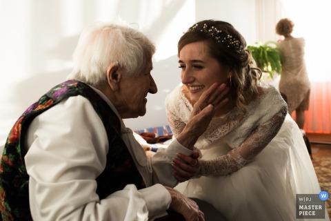 De bruid neemt de arm van een man terwijl hij haar gezicht aanraakt op deze foto door een huwelijksfotograaf uit Malopolskie, Polen.
