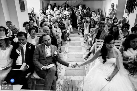 在倫敦,英國婚禮報告攝影師的這張黑白照片中,新娘和新郎在儀式期間牽著手穿過過道。