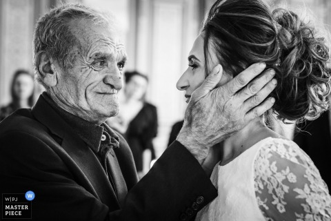 Black and white photo of a man holding the bride's face by a France wedding photographer.