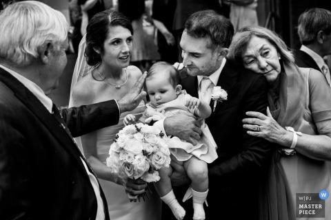 Photo noir et blanc du manège et du marié tenant un bébé par un photographe de mariage à Rotterdam.