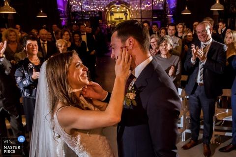 Photo de la mariée et du marié se touchant le visage pendant que les invités applaudissent à la fin de la cérémonie par un photographe de mariage de Rotterdam.