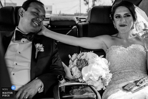 Zdjęcie panny młodej dotykającej twarzy pana młodego, gdy siedzą z tyłu pojazdu przez fotografa ślubnego z Limy w Peru.