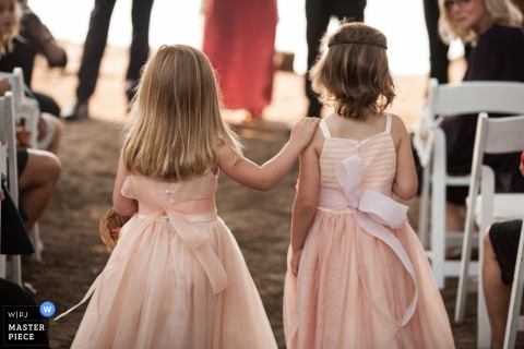 A San Francisco, California wedding photograph of two little girls in pink dresses walking down the aisle while the girl on the left is putting her hand on the other's shoulder