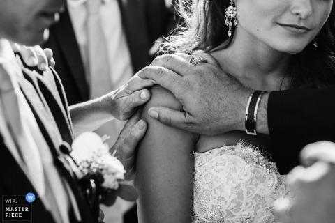 Schwarzweiss-Hochzeitsfoto Lissabons, Portugals des Bräutigams, des Priesters und eines anderen Gastes, die ihre Hände auf die Schulter der Braut setzen