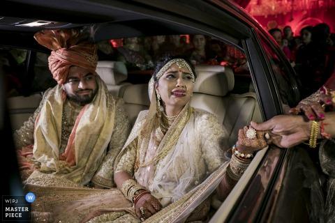 De bruid wordt emotioneel als ze een vrouwenhand door haar autoraam op deze foto neemt van een huwelijksfotograaf uit Montpellier.