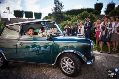 The bride waves to the guests from inside a small, green car in this send-off photo by a Morbihan wedding photographer.