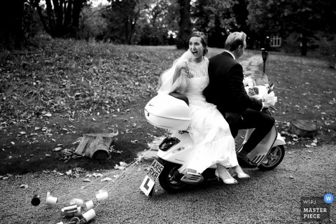 Die Braut und der Bräutigam fahren auf einem Motorrad weg, während Dosen hinter ihnen in diesem Schwarzweiss-Foto durch einen Hochzeitsreportagephotographen West Sussexs, England schleppen.