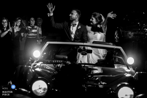 The bride and groom wave to their guests as they drive away in a car in this black and white photo by a Toronto, Ontario wedding photographer.