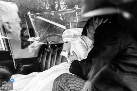 The bride and groom kiss in the back seat of a vehicle in this black and white photo by a London, England wedding reportage photographer.
