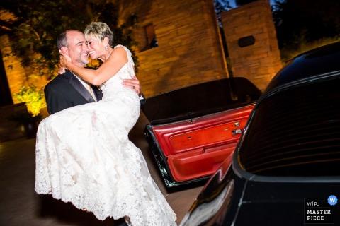Le marié porte la mariée à une voiture sur cette photo par un photographe de mariage en Arizona.